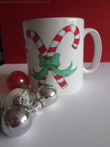 This Candy Cane Mug features a design by Jackie Evans of Jac's Little Welsh Studio